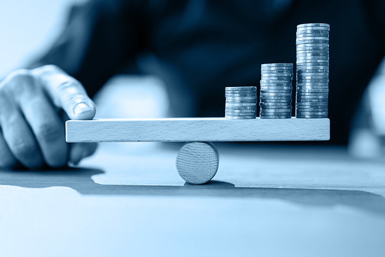 mano en una balanza con monedas